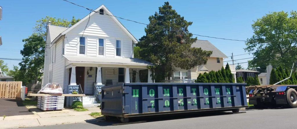 hometown-waste-dumpster-on-wood-planks-for-roofing-job