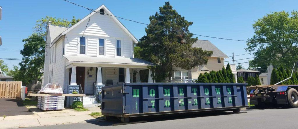 hometown-waste-dumpster-on-wood-planks-for-roofing-job